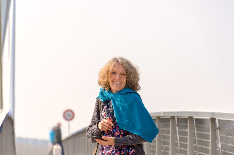 Portrait of smiling woman standing against railing and sky