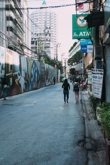 Rear view of people walking on street amidst buildings in city