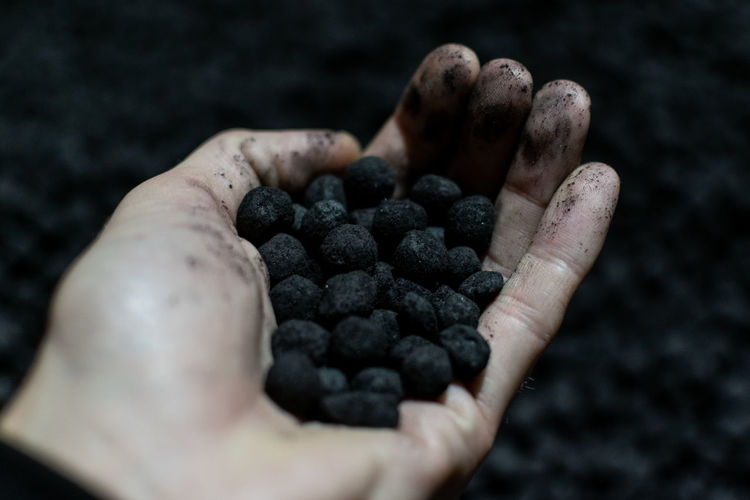 Close-up of hand holding iron ore pellets.