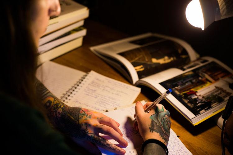 High angle view of woman writing book on table