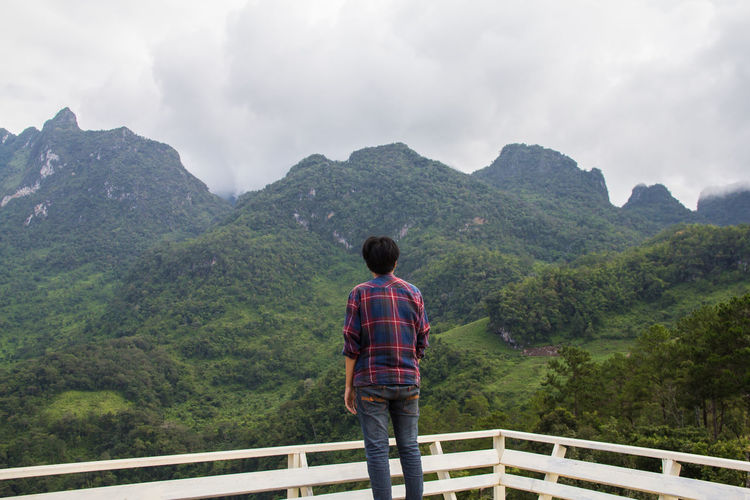 Rear view of man standing by railing against mountains and sky