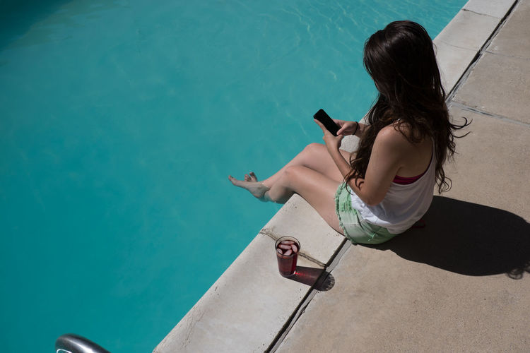 High angle view of woman using phone at poolside