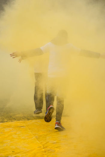 People walking amidst yellow powder paint during holi