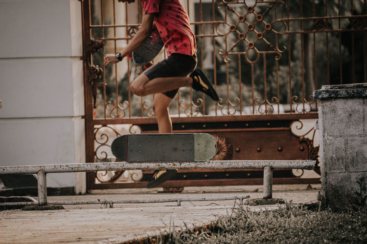 Low Section Of Man Skateboarding By Gate