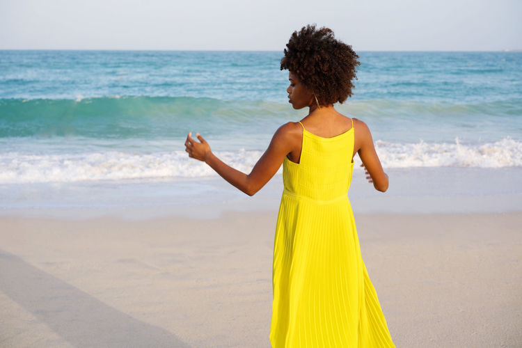 Low angle shot beautiful black woman with afro wearing yellow dress against blue sky