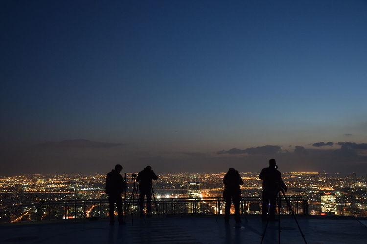 Silhouette people on terrace overlooking illuminated cityscape at dusk
