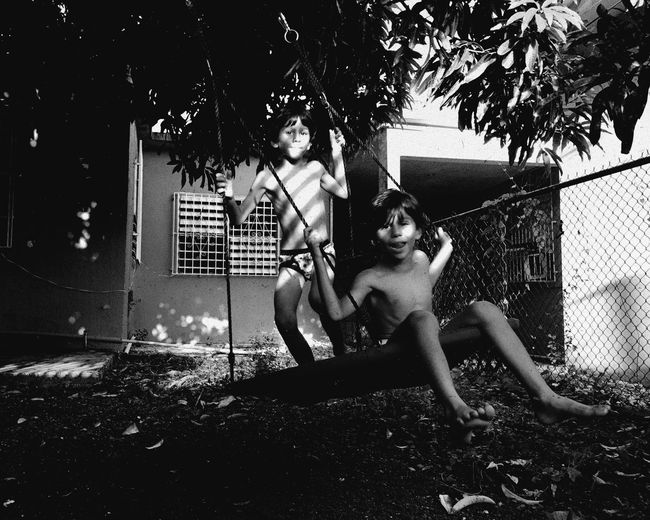 Portrait of shirtless brothers swinging in yard