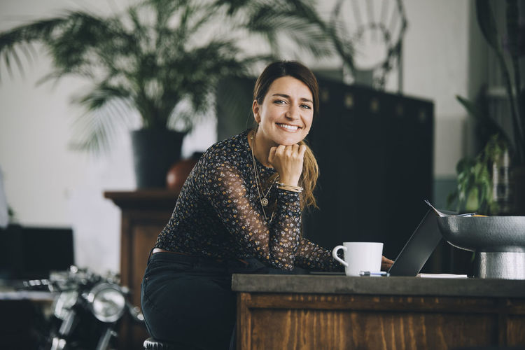 Portrait of a smiling woman sitting on table
