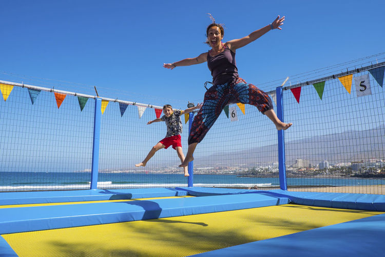 Cheerful woman jumping with son on trampoline against blue sky