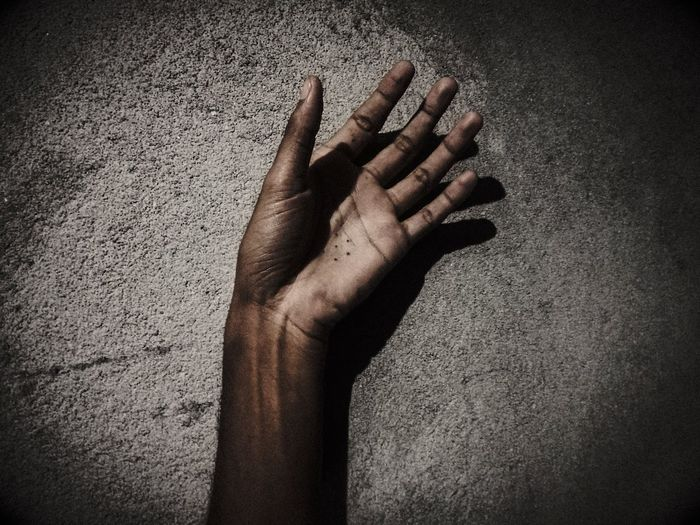 Cropped Hand Of Person Against Wall