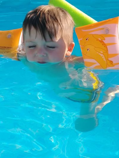 summer innocence Jasper Jasper! Jasper Sunsets Home Pool Water Blue Reflections In The Water Reflections ☀ Outside Son Adventures Wild Child Water Floaties Water Swimming Child Swimming Pool Childhood Portrait Headshot Summer Boys Wet Hair Floating On Water Floating Inflatable  Inflatable Ring