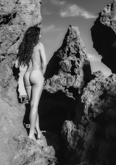 Rear view of naked woman standing on rock formation