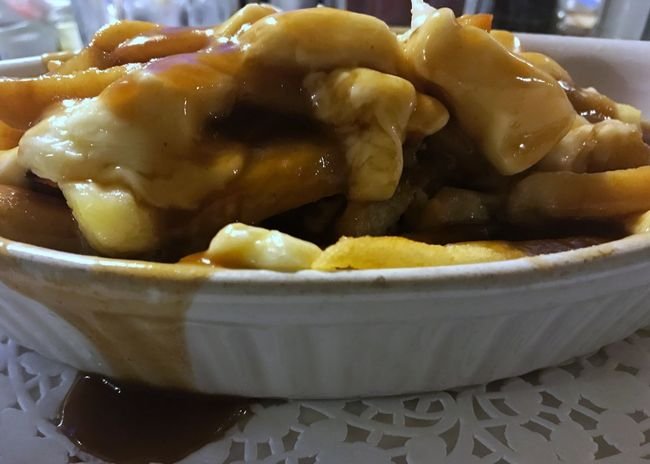 Poutine: French fries, cheese curds, and brown gravy. A Canadian delight. Poutine Food French Fries Brown Gravy Cheese Curds Food And Drink Bowl Close-up Doily Ready-to-eat Horizontal