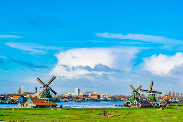 Traditional windmills on field by lake against blue sky