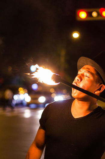 Fire-eater blowing fire on street at night