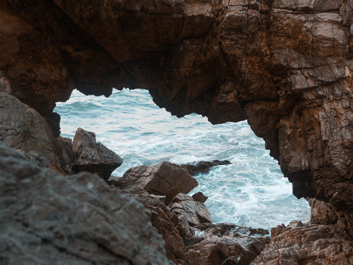 Scenic view of sea seen through cave