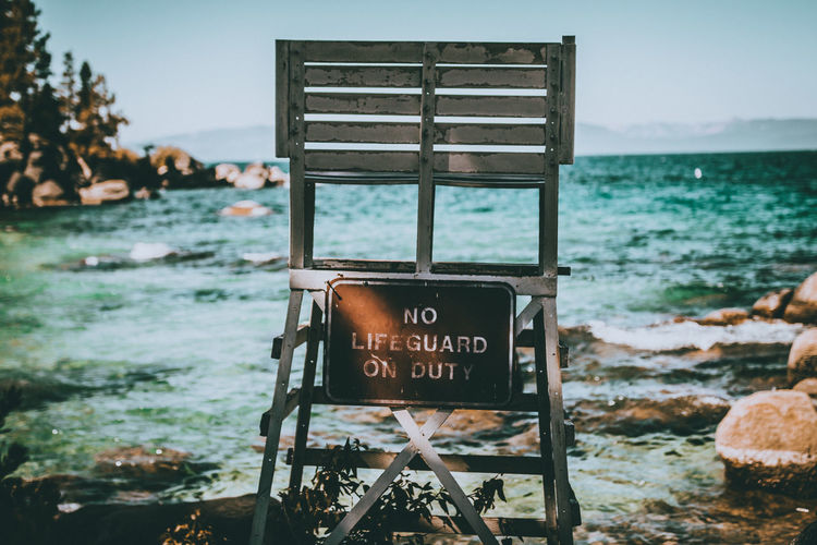 Lifeguard chair with warning message at beach against sky