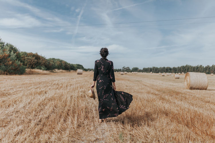 Rear View Of Woman On Agricultural Field Against Sky