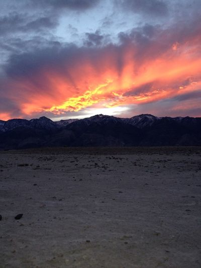 Scenic view of mountains against cloudy sky at sunset