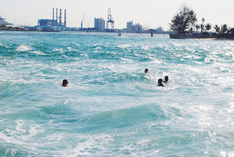 People Swimming In Rippled Sea, Industrial Area In Background