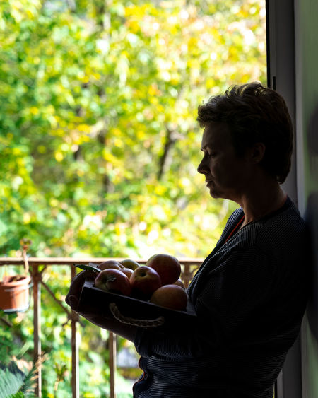 Woman holding apples in tray while standing at home