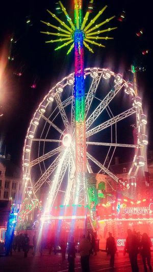 Arts Culture And Entertainment Night Ferris Wheel Multi Colored Illuminated Amusement Park Nightlife Celebration Fun Large Group Of People Enjoyment Amusement Park Ride Leisure Activity Sky Outdoors Disco Lights People