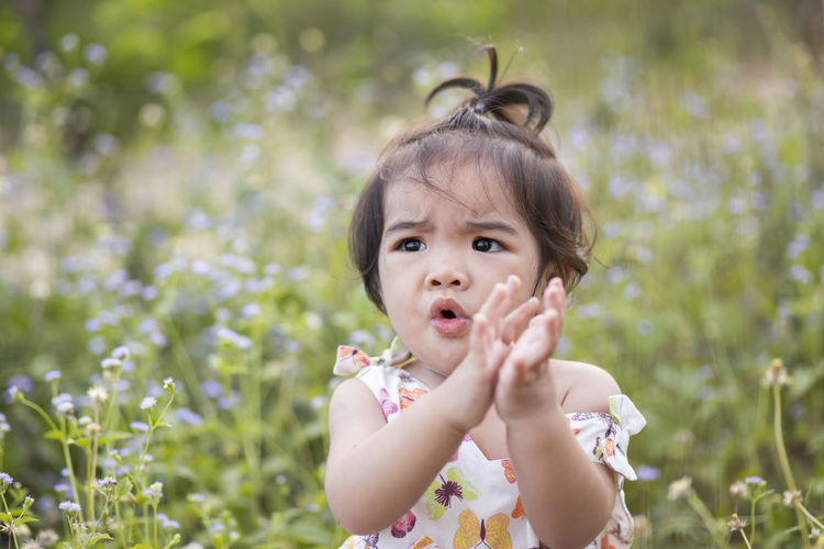 Portrait of cute baby girl against plants