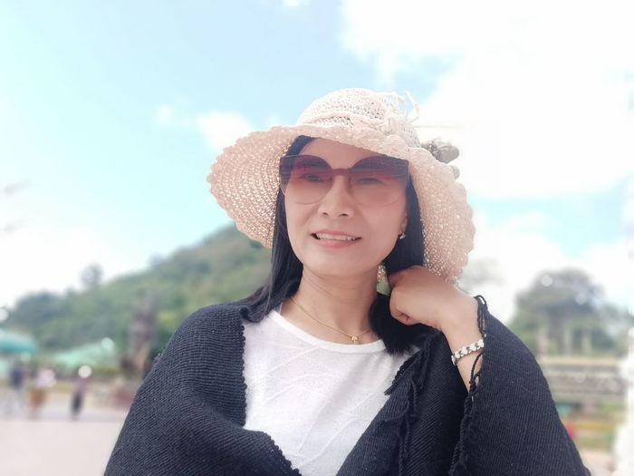 Portrait of smiling young woman wearing hat and sunglasses against sky