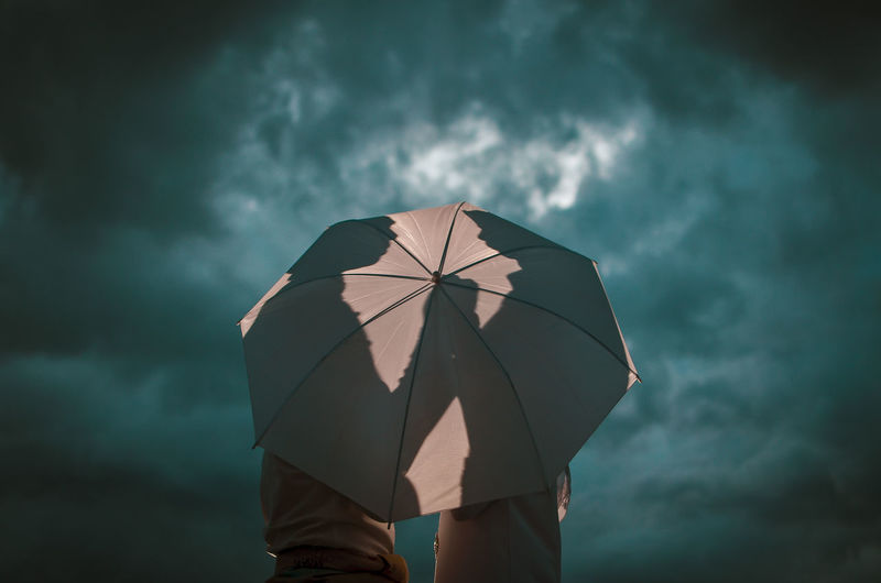 Low angle view of man holding umbrella against sky