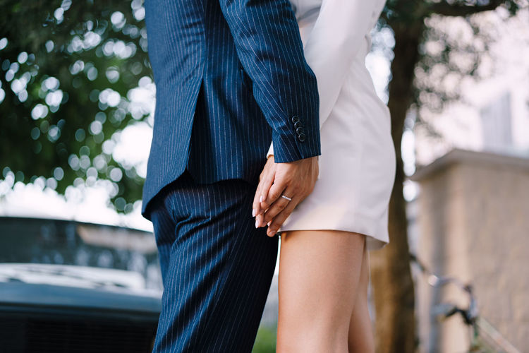 Midsection of couple standing against blurred background
