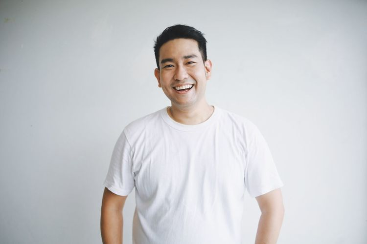 Portrait of smiling young man against white background