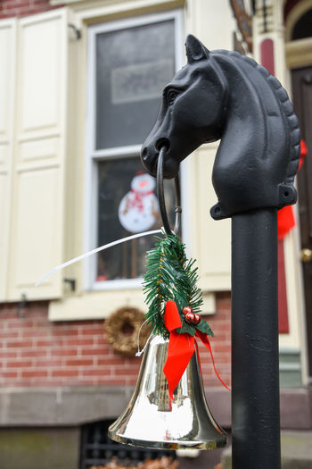 Hitching Post Beauty In Nature Brass Bell Building Exterior Christmas Christmas Decorations Close-up Day Depth Of Field Focus On Foreground Hitching Post Horse Head Iron Iron Horse No People Outdoors