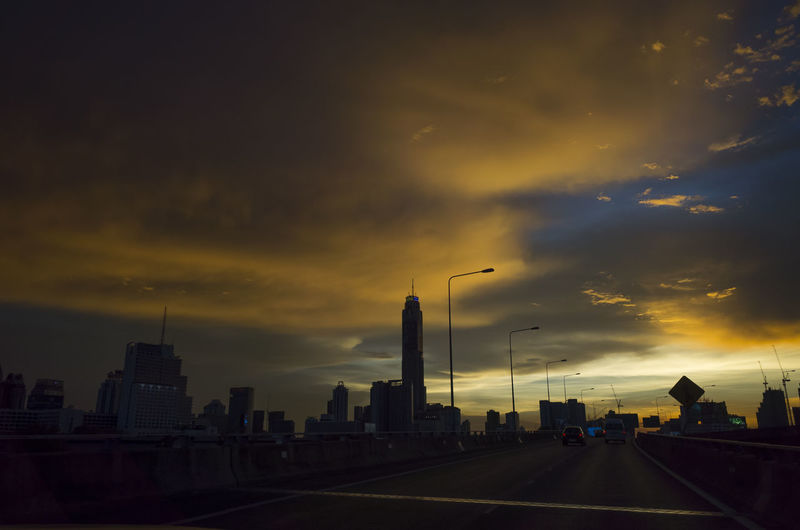 Sky Cloud - Sky Sunset Architecture City Building Exterior Built Structure Transportation Street Road Nature No People Building Street Light Mode Of Transportation Orange Color The Way Forward Dramatic Sky Cityscape Outdoors Office Building Exterior Skyscraper