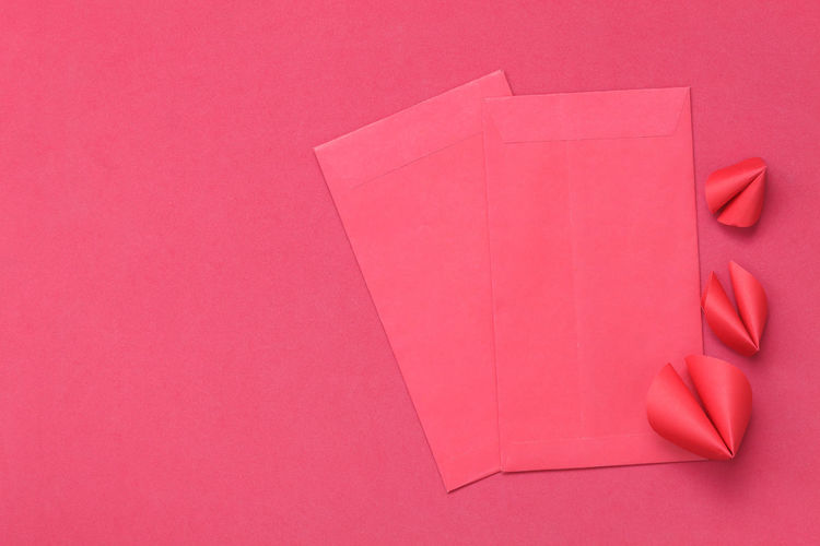 High angle view of envelops on pink background