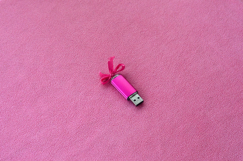 Close-up of usb stick on pink fabric