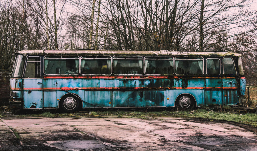Abandoned bus against bare trees
