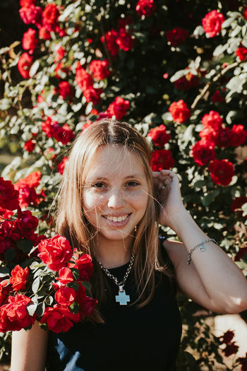 Portrait of a smiling girl with red flowers
