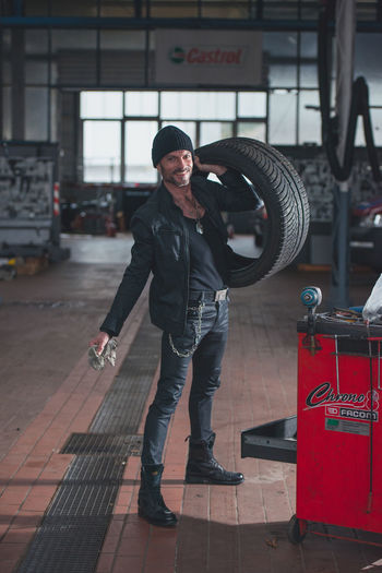 One Person Real People Standing Casual Clothing Men Indoors  Young Men Full Length Front View Day Young Adult Transportation Auto Repair Shop Looking At Camera Occupation Holding Focus On Foreground Working Wheel