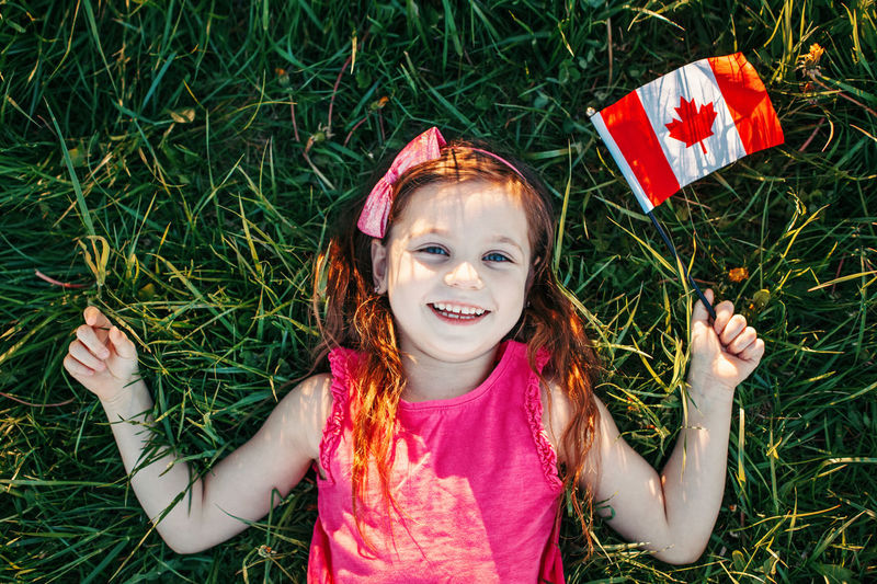 Happy girl with canadian flag lying on field