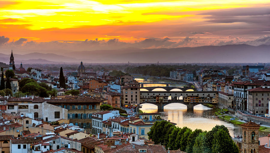 Ponte vecchio bridge over canal amidst buildings during sunset