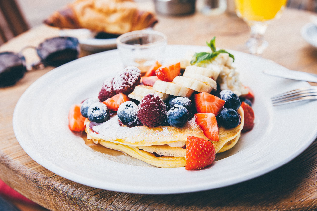 Close-Up Of Pancake With Fruits In Plate On Table