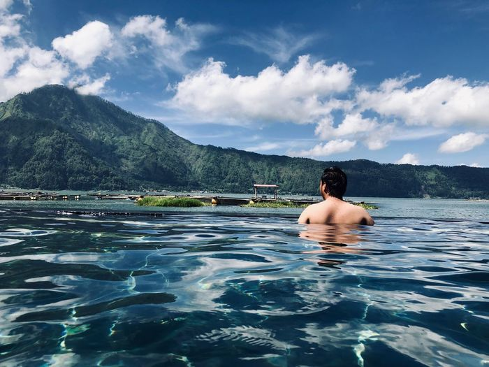 Rear view of shirtless man in infinity pool by lake