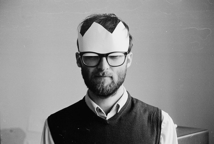 Portrait Of Man Wearing Paper Crown And Glasses