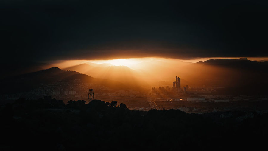 Silhouette of buildings in city during dramatic sunset