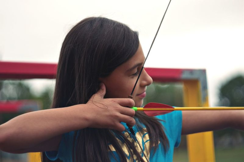 Close-up of happy girl practicing archery against sky