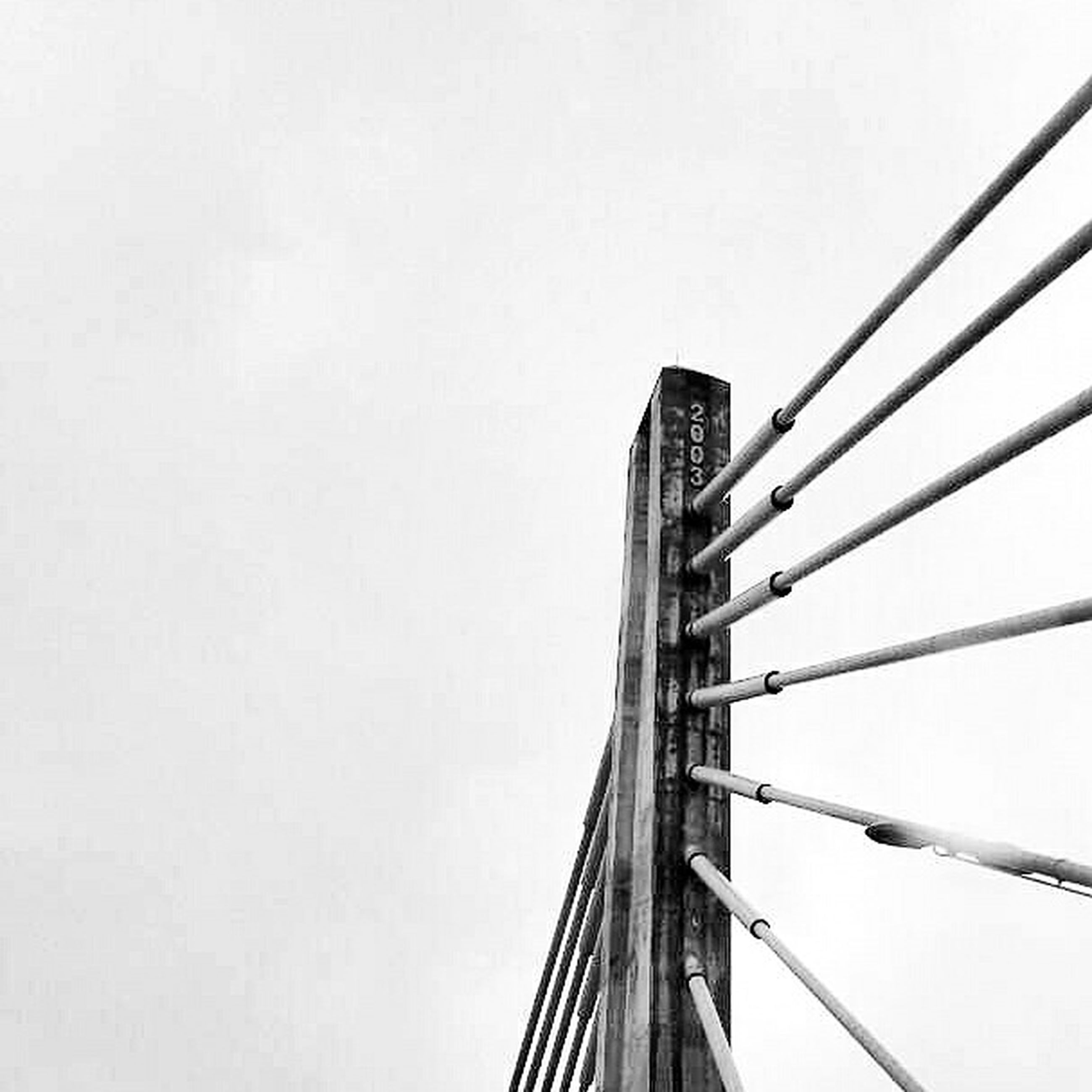 low angle view, clear sky, connection, built structure, copy space, architecture, engineering, metal, tall - high, suspension bridge, metallic, day, outdoors, no people, bridge - man made structure, tower, development, high section, sky, tall