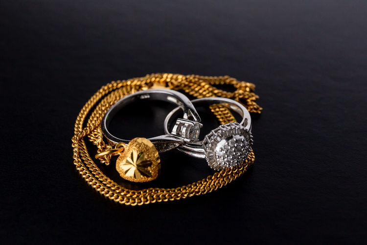 High angle view of wedding rings on table against black background