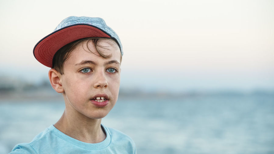 Young blue eyed boy wearing a cap and looking in the distance Beach Boys Childhood Day Focus On Foreground Headshot Horizon Over Water Nature One Person Outdoors People Portrait Real People Sea Sky Water