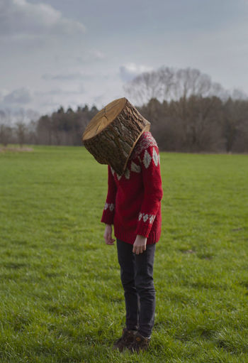 Woman With Face Covered By Wood Standing On Grassy Field