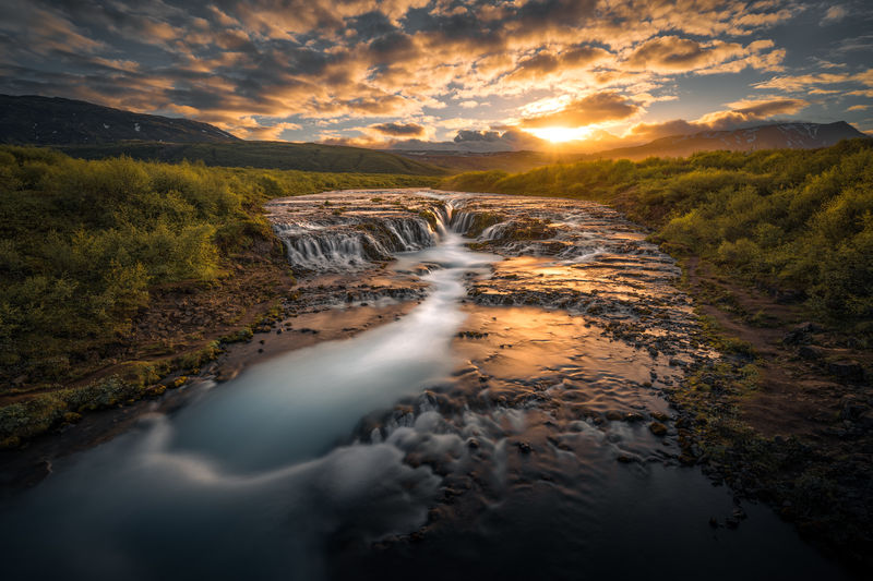 Stream flowing amidst trees against sky during sunset